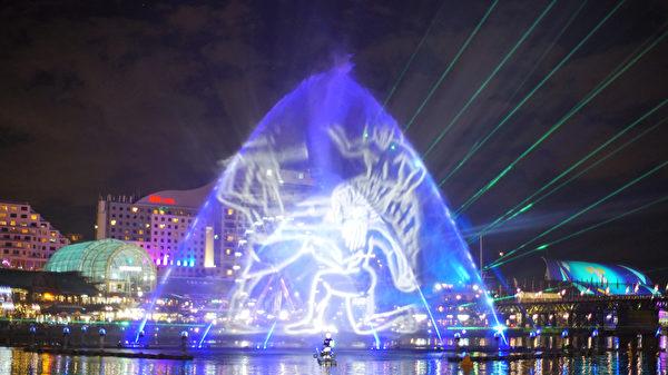 融合灯光师、作曲家、喷泉工程师和焰火设计师等合作设计出巨大喷泉水幕上,投影多样灯光图像。(周东/大纪元)