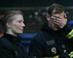 6月14日伦敦格伦菲尔塔楼发生火灾,200名消防员参与救火,图为14日当天在火灾现场的两名消防员。(DANIEL LEAL-OLIVAS/AFP/Getty Images)