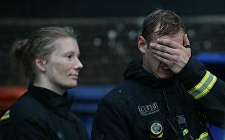 6月14日倫敦格倫菲爾塔樓發生火災,200名消防員參與救火,圖為14日當天在火災現場的兩名消防員。(DANIEL LEAL-OLIVAS/AFP/Getty Images)