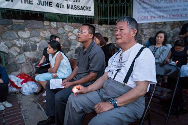 中國民主運動海外聯席會議主席魏京生(右一)手持蠟燭,悼念為民主自由獻身的人士。(石青雲/大紀元)
