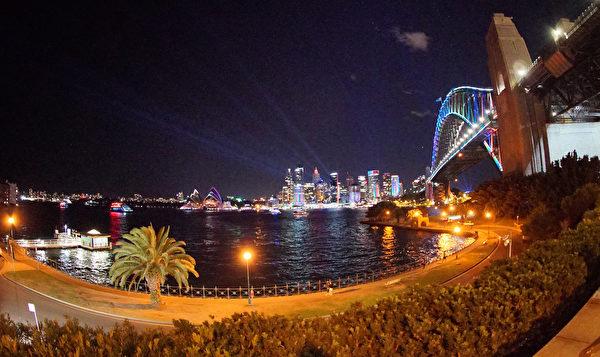 悉尼著名的海港大橋上,燈光忽明忽暗,變換著多彩顏色,與地標建築悉尼歌劇院共同構成水上的一道風景。(周東/大紀元)