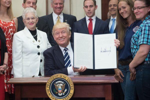 川普(中)15日簽署新行政令,放寬學徒計畫的限制,為美國人民提供更多的就業機會。 (AFP)