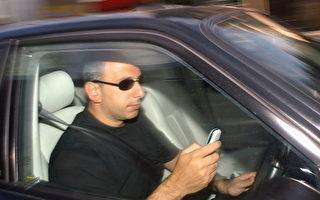 一名男子在驾车时发手机短信。 (Bruno Vincent/Getty Images)