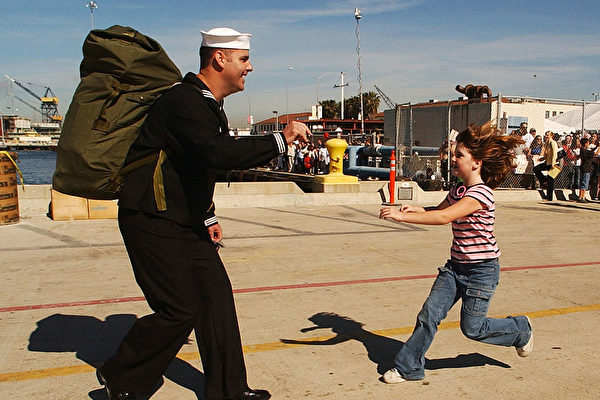 2009年,从阿富汗战场归来的英国士兵得到了女儿的热情迎接。(Matt Cardy/Getty Images)