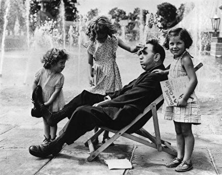 1951年8月6日,一位疲累的父亲得到三个女儿殷勤地照顾:一个女儿为父亲脱鞋,另一位在擦汗,还有一个女儿拿来故事书给父亲看。(Fox Photos/Getty Images)