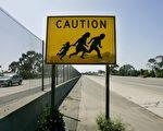 川普旅行行政令近期或在高院開始審理。圖為5月13日的美墨邊境處,一個警示牌顯示,這個路段常有行人穿越。 (Sandy Huffaker/Getty Images)