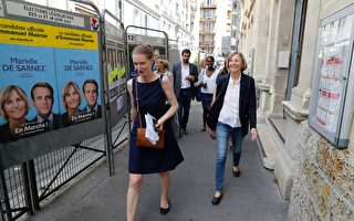French Minister of European Affairs Marielle de Sarnez (R) walks past election campaign posters picturing herself and French President Emmanuel Macron for the La Republique En Marche party as she leaves a polling station after casting her vote in Paris during the first round of the French legislative elections on June 11, 2017. / AFP PHOTO / Patrick KOVARIK        (Photo credit should read PATRICK KOVARIK/AFP/Getty Images)