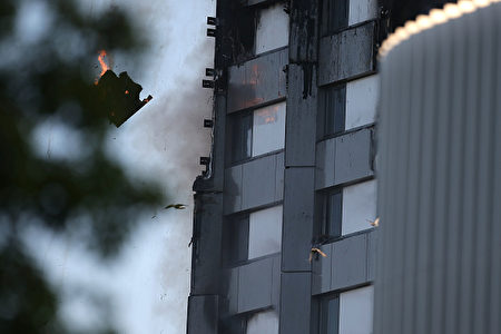 "TOPSHOT - An arm holding a cloth can be seen waving from a window of Grenfell Tower as a piece of burning debris falls on June 14, 2017 in west London. The massive fire ripped through the 27-storey apartment block in west London in the early hours of Wednesday, trapping residents inside as 200 firefighters battled the blaze. Police and fire services attempted to evacuate the concrete block and said ""a number of people are being treated for a range of injuries"", including at least two for smoke inhalation. / AFP PHOTO / Daniel LEAL-OLIVAS (Photo credit should read DANIEL LEAL-OLIVAS/AFP/Getty Images)"