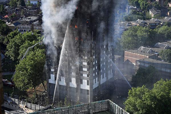 消防员从地面浇水灭外墙的火。图片摄于6月14日,当天凌晨火灾爆发。(Leon Neal/Getty Images)