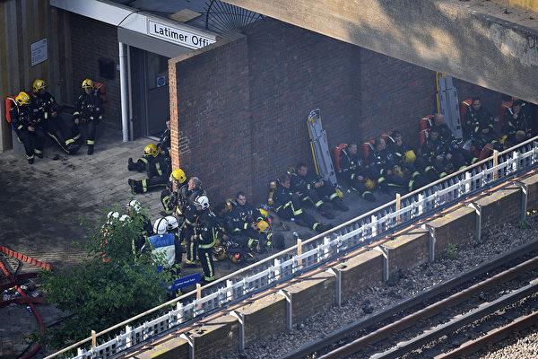 6月14日凌晨,伦敦24层的住宅楼格伦费尔塔楼陷入一片火海之中,超过200名消防员到现场灭火救人。图为当天白天精疲力尽的消防员在塔楼附近休息,等待着进入大楼开展下一轮的救人行动。 (Leon Neal / Getty Images)