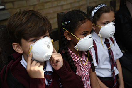 LONDON, ENGLAND - JUNE 14: Young children wear protective face masks near the burning 24 storey residential Grenfell Tower block in Latimer Road, West London on June 14, 2017 in London, England. The Mayor of London, Sadiq Khan, has declared the fire a major incident as more than 200 firefighters are still tackling the blaze while at least 50 people are receiving hospital treatment. (Photo by Carl Court/Getty Images)