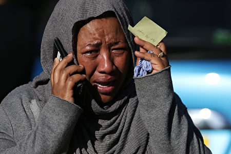 "A woman cries as she tries to locate a missing relative suspected of being affected by the massive fire that engulfed Grenfell Tower, a residential block on June 14, 2017 in west London. The massive fire ripped through the 27-storey apartment block in west London in the early hours of Wednesday, trapping residents inside as 200 firefighters battled the blaze. Police and fire services attempted to evacuate the concrete block and said ""a number of people are being treated for a range of injuries"", including at least two for smoke inhalation. / AFP PHOTO / Daniel LEAL-OLIVAS (Photo credit should read DANIEL LEAL-OLIVAS/AFP/Getty Images)"