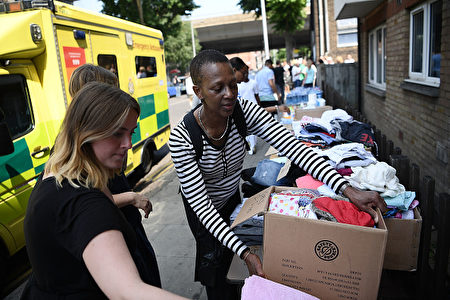 LONDON, ENGLAND - JUNE 14: Women donate clothes to a stall which has been set up to help people near the burning 24 storey residential Grenfell Tower block in Latimer Road, West London on June 14, 2017 in London, England. The Mayor of London, Sadiq Khan, has declared the fire a major incident as more than 200 firefighters are still tackling the blaze while at least 50 people are receiving hospital treatment. (Photo by Carl Court/Getty Images)