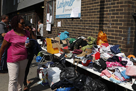 Clothes are offered to those affected by the fire that ripped through Grenfell Tower, a residential block in west London on June 14, 2017. At least six people were killed Wednesday when a massive fire tore through a London apartment block overnight, with survivors voicing anger over longstanding safety fears at the 24-storey Grenfell Tower. / AFP PHOTO / Adrian DENNIS (Photo credit should read ADRIAN DENNIS/AFP/Getty Images)