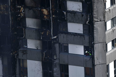 A fireman is seen at a window of the Grenfell Tower after a fire ripped through the building in west London on June 14, 2017. At least six people were killed Wednesday when a massive fire tore through a London apartment block overnight, with survivors voicing anger over longstanding safety fears at the 24-storey Grenfell Tower. / AFP PHOTO / Ben STANSALL (Photo credit should read BEN STANSALL/AFP/Getty Images)