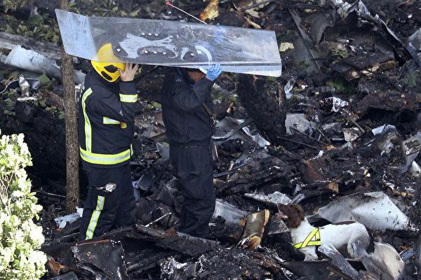消防员和嗅探犬于2017年6月15日在伦敦格伦费尔大楼脚下检查碎片,头顶钢化玻璃板,以防从上面掉下东西被砸到。14日凌晨,24层的住宅楼格伦费尔大楼被火焰吞没,79人死亡。 (Dan Kitwood / Getty Images)