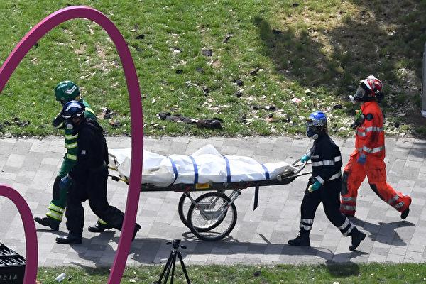 警察和消防员将一名伦敦大火死者抬走,图片摄于6月16日,大火第三天。(CHRIS J RATCLIFFE/AFP/Getty Images)
