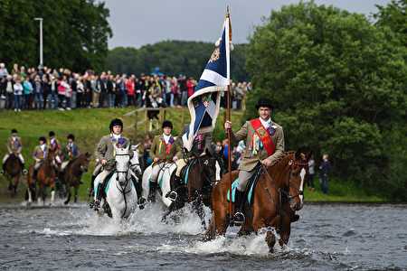 SELKIRK, SCOTLAND - JUNE 16: Standard bearer Kieran Riddell fords the river Ettrick with his attendants as they take part in the town's Common Riding, one of the oldest Borders festivals on June 16, 2017 in Selkirk ,Scotland. The event dating from the Battle of Flodden in 1513, remembers the story of Flodden, when Selkirk sent 80 men into battle with the Scottish King. One man returned, bearing a blood stained English flag. (Photo by Jeff J Mitchell/Getty Images)