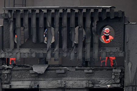 Members of a search and rescue team work near the top of the gutted Grenfell Tower, which was ravaged by fire, in west London on June 16, 2017. The toll from the London tower block fire has risen to at least 30 people dead and the flames have now been extinguished, police said on June 16, 2017. / AFP PHOTO / Chris J Ratcliffe (Photo credit should read CHRIS J RATCLIFFE/AFP/Getty Images)