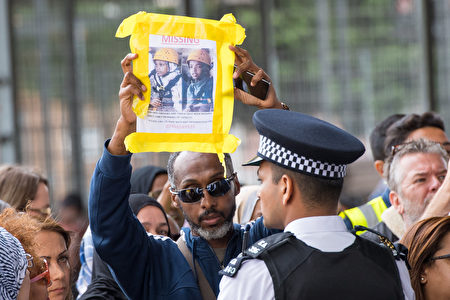 LONDON, ENGLAND - JUNE 16: A man holds up a missing persons poster during a visit by Queen Elizabeth II and Prince William, Duke of Cambridge to the Westway Sports Centre, which is providing temporary shelter for those who have been made homeless in the Grenfell Tower disaster. on June 16, 2017 in London, England. 30 people have been confirmed dead and dozens still missing, after the 24 storey residential Grenfell Tower block in Latimer Road was engulfed in flames in the early hours of June 14. Emergency services will spend a third day searching through the building for bodies. Police have said that some victims may never be identified. (Photo by Dominic Lipinski - WPA Pool /Getty Images)
