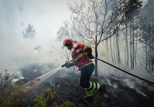 TOPSHOT - A firefighter uses a hose to combat a wildfire in Vale da Ponte, Pedrograo Grande, on June 20, 2017. The huge forest fire that erupted on June 17, 2017 in central Portugal killed at least 64 people and injured 135 more, with many trapped in their cars by the flames. / AFP PHOTO / MIGUEL RIOPA (Photo credit should read MIGUEL RIOPA/AFP/Getty Images)