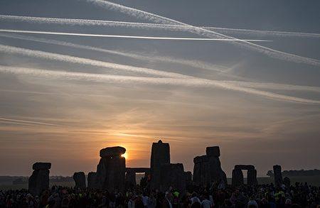 6月21日夏至日的早晨,大批人聚集在巨石陣等待日出。這個活動的歷史可以追溯到幾千年以前。人們到現在還不清楚巨石陣存在的目的,但是人們知道在夏至日這天,光線會從巨石陣前方像拱門一樣的鞋跟石中間直射到巨石陣中間的祭壇石。人們一邊觀看這個奇景,一邊感嘆古人的智慧。(CHRIS J RATCLIFFE/AFP/Getty Images)