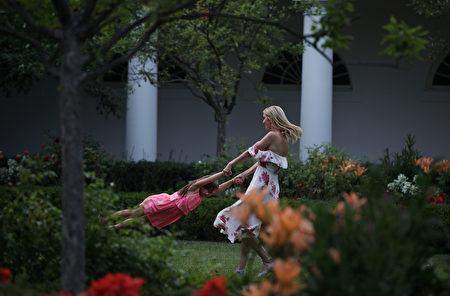 2017年6月22日,伊万卡(右)在白宫玫瑰园和女儿拉手玩转圈。白宫当天在南草坪举行野餐活动。 (Alex Wong/Getty Images)