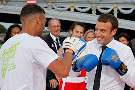法国总统马克龙与拳击选手合作为争办奥运出力。 (JEAN-PAUL PELISSIER/AFP/Getty Images)