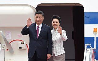 国家主席习近平与夫人彭丽媛步出机舱。(ANTHONY WALLACE/AFP/Getty Images)