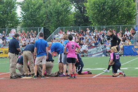 比賽開始不久,記者隊一名隊員受傷,議員隊隊員單膝下跪。(林樂予/大紀元)