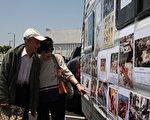 仔细阅读中共恐怖暴行图片的民众张氏夫妇。(徐绣惠/大纪元)