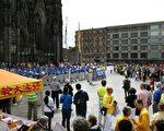 6月25日在科隆的法輪功大遊行從著名景點——科隆大教堂前開始,圖為天國樂團演奏,人們圍觀。(曹工/大紀元)