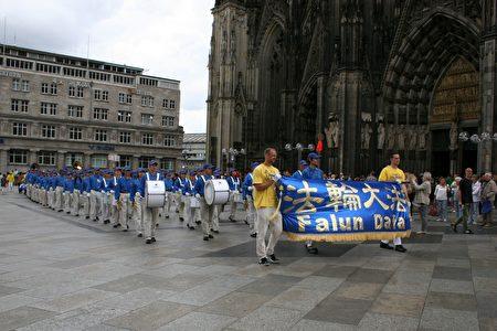 法轮功学员的方阵离开科隆大教堂前的广场,前往老市场。天国乐团打头阵。(曹工 /大纪元)