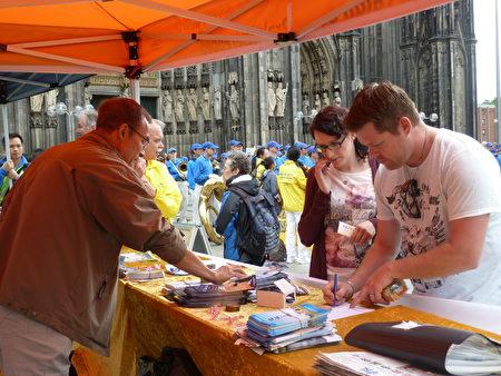 在科隆大教堂前,当场有路人签名反对中共活摘法轮功学员器官。(曹工 /大纪元)