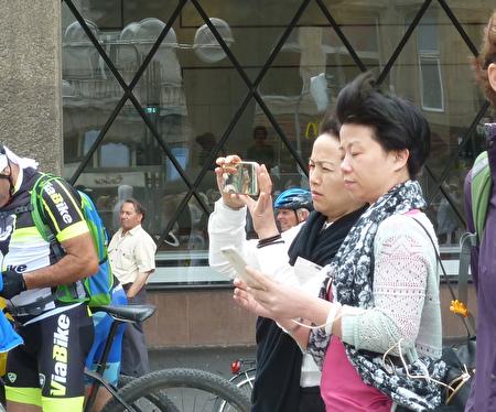 两位中国大陆游客在科隆大教堂前拍摄法轮功学员的方阵,一位已经拍完,正在检查拍摄效果,一位正在拍摄。(文婧/大纪元)