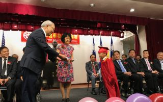 毕业典礼上,毕业生向华侨学校董事长、中华公所主席萧贵(左一)源鞠躬行礼。 (林丹/大纪元)