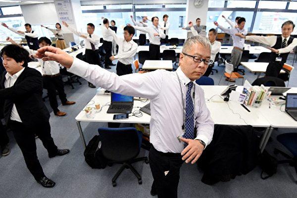 有越来越多日本公司鼓励员工在休息时做体操或运动,以期保持身体灵活和健康。图为东京Adoc公司的员工在做伸展操。(TORU YAMANAKA / AFP)