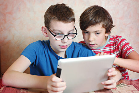 过多使用平板电脑、手机,儿童近视数量大增。(Shutterstock)