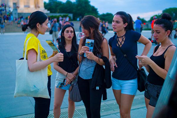 法轮功学员向游客讲述在中国发生的迫害。(Mark Zou/大纪元)