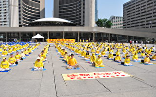 7月21日,近千名法轮功学员及支持者在加拿大多伦多市中心集会。图为,集会前,学员在集体炼功。(周行/大纪元)