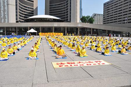 7月21日,近千名法輪功學員及支持者在加拿大多倫多市中心集會。圖為,集會前,學員在集體煉功。(周行/大紀元)