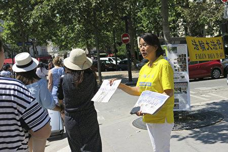 孫景虹在法國向中國大陸遊客講法輪功真相,發放給他們真相資料。(關宇寧/大紀元)