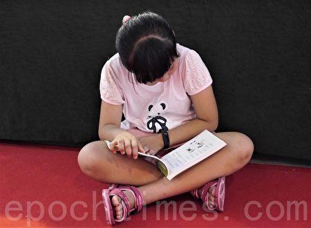 小朋友专心看书。(方金媛/大纪元)