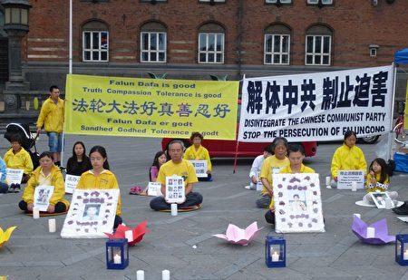 2017年7月20日晚,丹麦法轮功学员在首都市政厅前点燃蜡烛,追悼在中共18年残酷迫害中失去生命的中国法轮功学员。(林达/大纪元)
