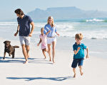Family playing with pet on the beach. Happy beautiful family running at beach with pet dog. Smiling parents with son and daughter having fun at seaside.(fotolia)