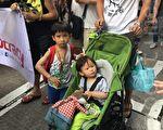 从事工程行业的市民黎先生,带分别2岁和6岁的小朋友上街游行,2岁小朋友手抱着一只狼的毛公仔。(黄瑞秋/大纪元)