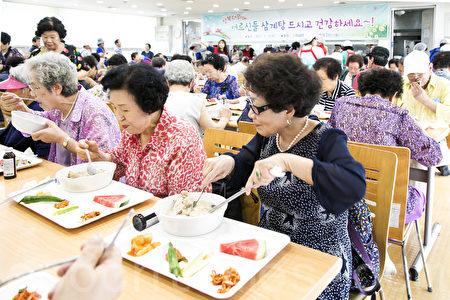 7月12日是初伏,初伏天韓國有吃參雞湯滋補身體的習慣。這一天中午,韓國首爾東大門區準備了熱乎乎的參雞湯為900名孤寡老人及生活生活困難老人效勞。(全景林/大紀元)