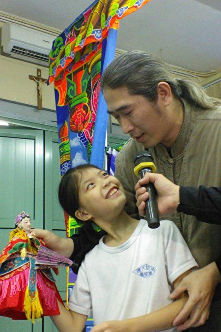 黄世志艺师指导小朋友如何操偶。(黄世志提供)