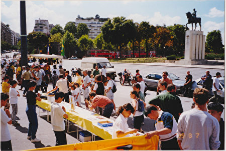 1999年8月7日,法國法輪功學員在巴黎人權廣前的人行道上向過往民眾展示法輪功功法,告訴人們法輪功的真實情況。(法輪功學員提供)