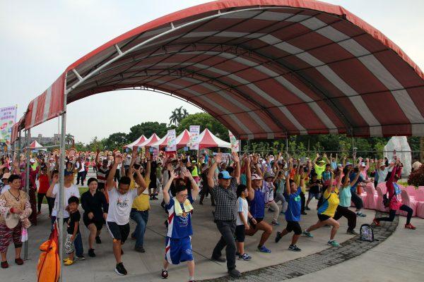 16日106年運動i臺灣計畫 -- 嘉義市全民動起來健走活動暨青少年體育發表嘉年華會在嘉義市香湖公園熱鬧登場,參與的民眾認真做暖身運動。 (嘉義市政府提供)